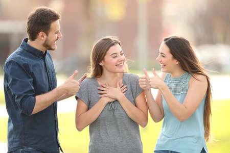 Zwei Freunde gratulieren einem glücklichen Mädchen, das auf der Straße steht