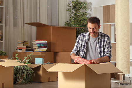 Happy man moving home unboxing belongings on the floor in the night Standard-Bild