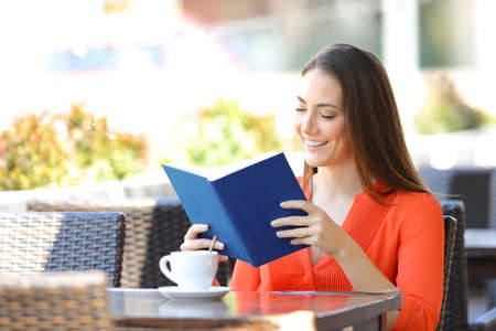 Happy woman relaxing reading a book sitting in a coffee shop terrace Stock Photo