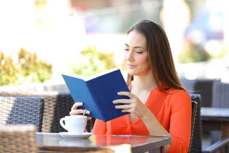 Serious woman relaxing reading a book sitting in a coffee shop terrace Banco de Imagens - 122060827