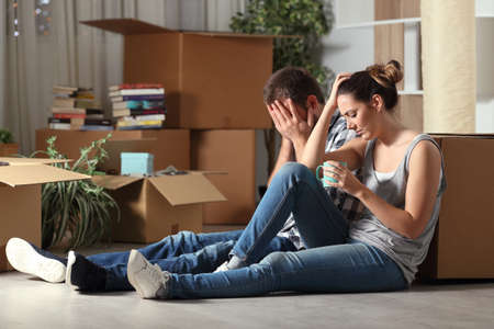 Sad evicted couple moving home complaining sitting on the floor in the night Stockfoto