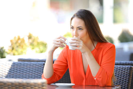 Relaxed and distracted woman drinking coffee looking away sitting in a bar terrace