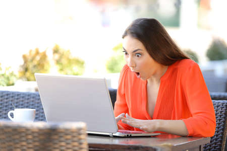 Amazed woman finding surprising content on a laptop sitting in a coffee shop terrace Stock Photo