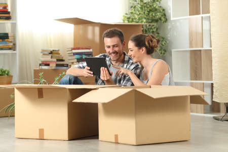Happy couple moving home checking tablet content sitting on the floor Stock Photo