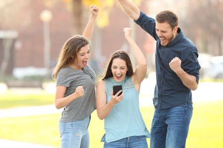 Front view portrait of 3 excited friends jumping reading good netw on phone 스톡 콘텐츠