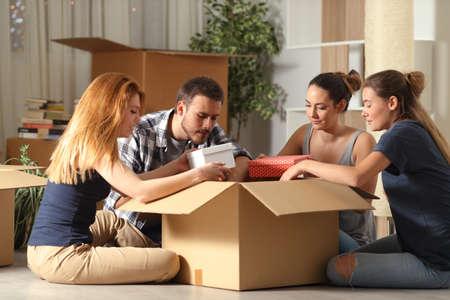 Vier ernsthafte Mitbewohner, die ihre Sachen auspacken und nachts auf dem Boden sitzend nach Hause ziehen