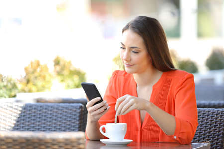 Woman stirring coffee checking smart phone content sitting in a bar terrace Foto de archivo