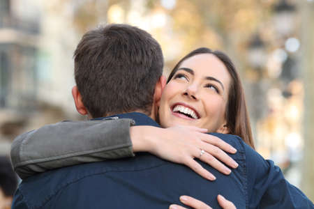 Happy girl hugs her boyfriend after meeting in a city street