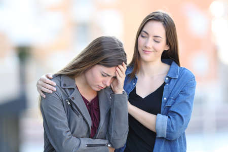 Hypocrite bad woman comforting her sad friend who is complaining in the street Stock Photo