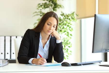 Employé de bureau sérieux écrivant sur un document sur un bureau sur le lieu de travail Banque d'images
