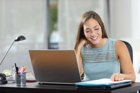 Mujer feliz trabajando leyendo documentos en un escritorio en casa