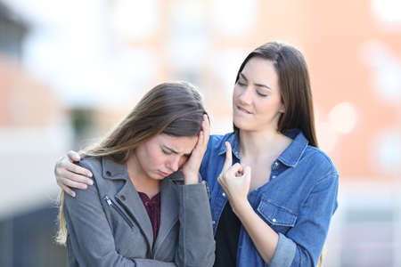 Sad woman being comforted by a bad friend in the street Stock Photo