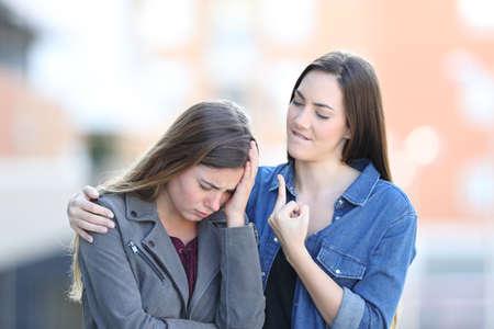 Traurige Frau, die von einem schlechten Freund auf der Straße getröstet wird