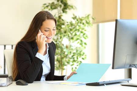 Glücklicher Büroangestellter, der das Dokument überprüft, das am Arbeitsplatz telefoniert
