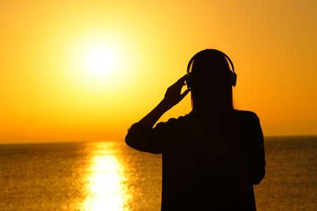 Vista posteriore ritratto di una silhouette di una donna che ascolta la musica al tramonto sulla spiaggia