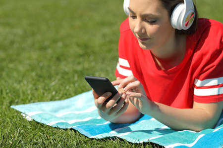 Serious girl in red listens to music browsing smart phone content on the grass