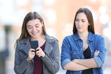 Front view portrait of an angry woman with her friend who is using phone in the street