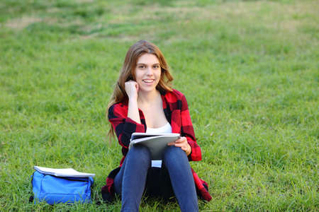 Happy student looks at camera sitting on the grass in a park