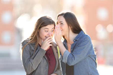 Gossip woman telling secret to her happy friend in the street