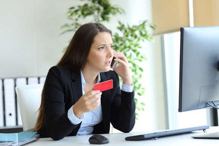 Exécutif inquiet détenant une carte de crédit réclamant au téléphone au bureau Banque d'images