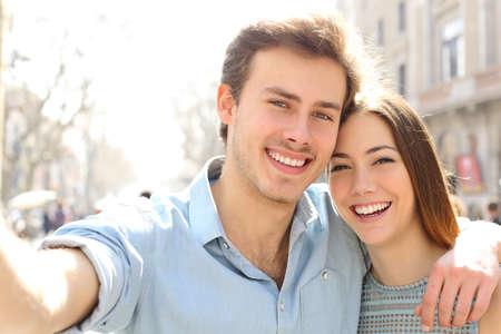 Feliz pareja está tomando selfies en la calle en vacaciones de verano en una gran ciudad Foto de archivo