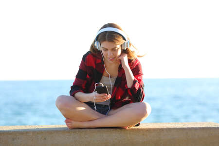 Front view full body portrait of a relaxed teen listening to music on the beach