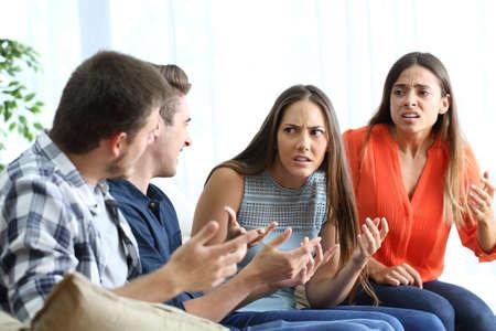 Cuatro amigos enojados peleando sentado en un sofá en casa