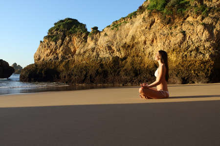 Full body profile of a woman relaxing practicing yoga on the beach Reklamní fotografie