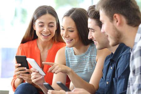 Feliz grupo de amigos comprobando teléfonos inteligentes sentado en un sofá en la sala de estar en casa
