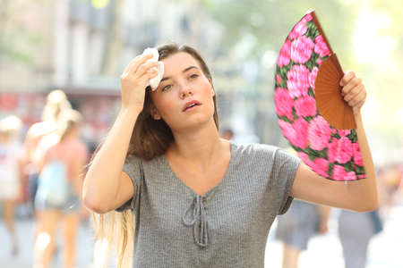 Front view portrait of a overwhelmed girl complaining suffering heat stroke in the street on summer