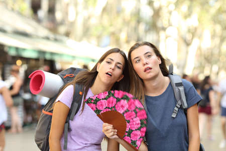 Two overwhelmed backpackers suffering heat stroke on summer vacation in the street Stock Photo