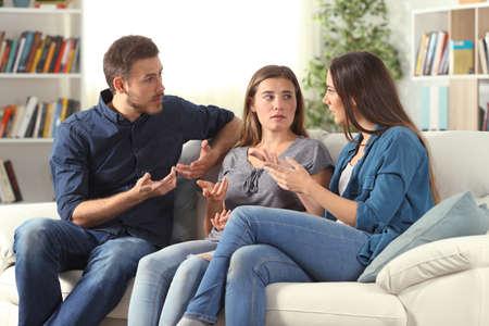 Drei ernsthafte Freunde, die sich zu Hause auf einer Couch im Wohnzimmer unterhalten Standard-Bild