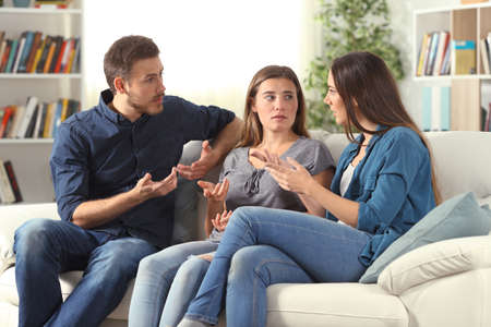 Three serious friends talking sitting on a couch in the living room at home Stock Photo
