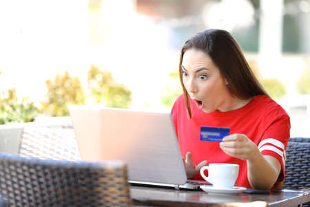 Shocked girl paying online with credit card and laptop sitting in a coffee shop terrace Stock Photo