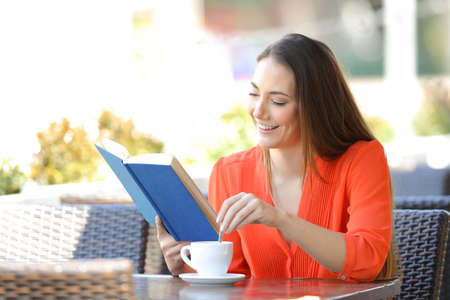 Happy woman relaxing reading a book stirring the coffee sitting in a bar terrace Stock Photo