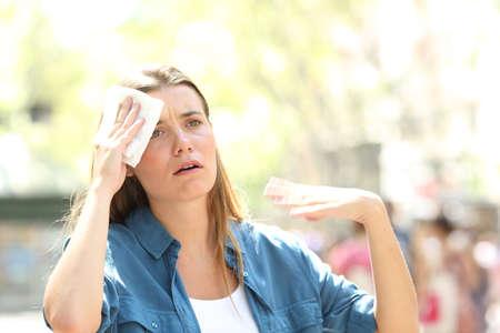 Ongelukkige vrouw die zweet door een hitteberoerte en in de zomer met de hand op straat wappert