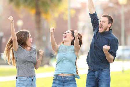 Front view portrait of three excited friends jumping celebrating success in a park 免版税图像