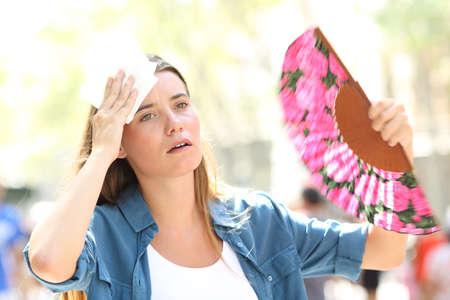 Donna triste che sventola e suda subendo un colpo di calore in estate per strada
