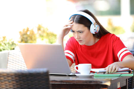 Worried student e-learning with a laptop and headphones sitting in a coffee shop terrace Banque d'images - 123603253