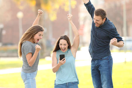Front view portrait of three excited friends jumping checking smart phone in a park Stockfoto