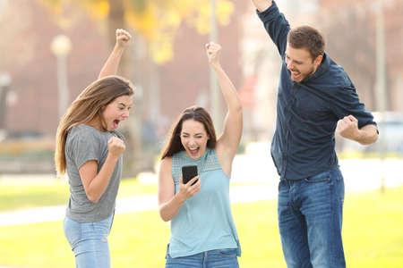 Retrato de vista frontal de tres amigos emocionados saltando comprobación de teléfonos inteligentes en un parque Foto de archivo