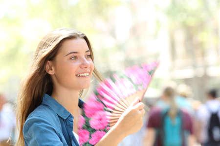 Happy woman fanning walking in the street on summer
