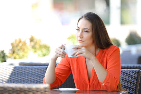 Angry woman holding mug looks away sitting in a coffee shop terrace