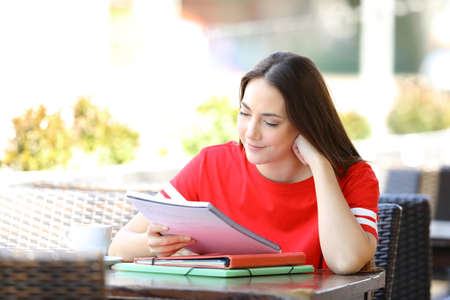 Satisfied student in red studying reading notes sitting in a bar terrace