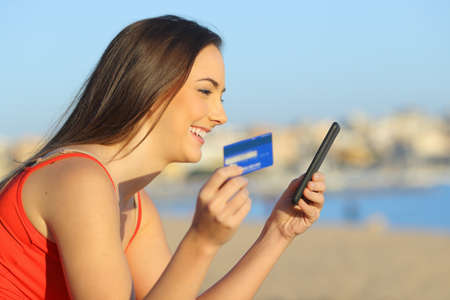 Profile of a girl paying online with a smart phone on the beach a sunny day
