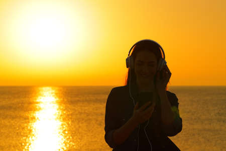 Front view of a woman silhouette listening to music at sunset on the beach Archivio Fotografico - 125066321