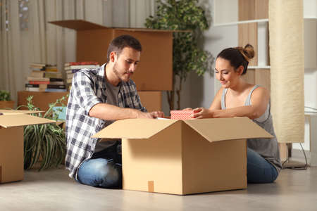 Serious couple boxing belongings moving house sitting on the floor in the night Stock Photo