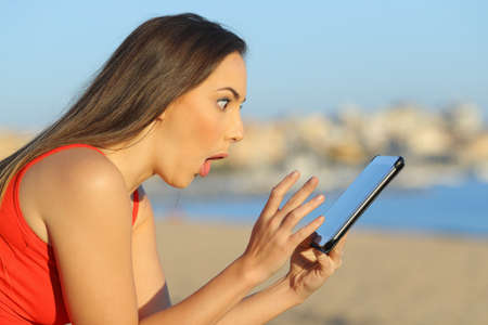 Surprised teen finding amazing content on tablet on the beach a sunny day Archivio Fotografico - 125066323