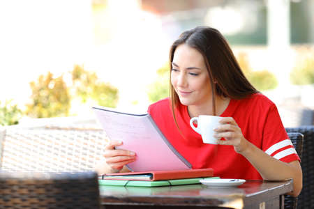 Student memorizing notes holding a coffee cup sitting in a bar terrace