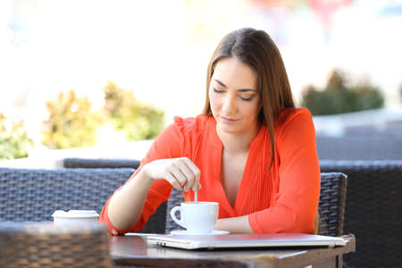 Serious woman sitting in a coffee shop terrace stirring the drink